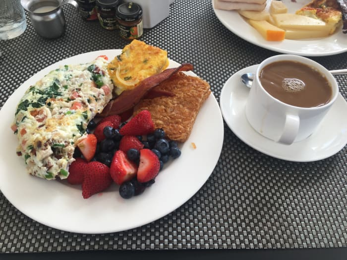 Breakfast of mixed berries, hashbrowns, egg white omelette, bacon and coffee