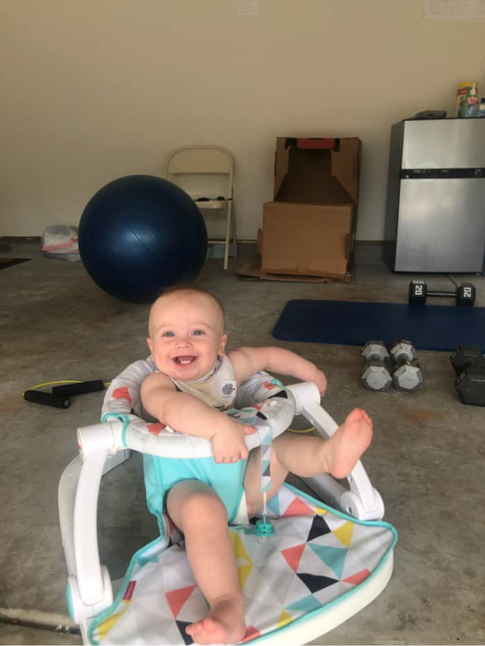 Jacob smiling sitting in his sit-me-up chair in the garage during a workout