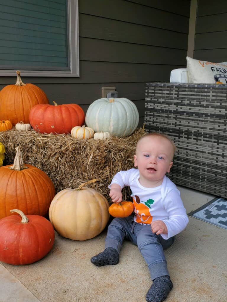 Jacob sitting on the patio next to the pumpkins