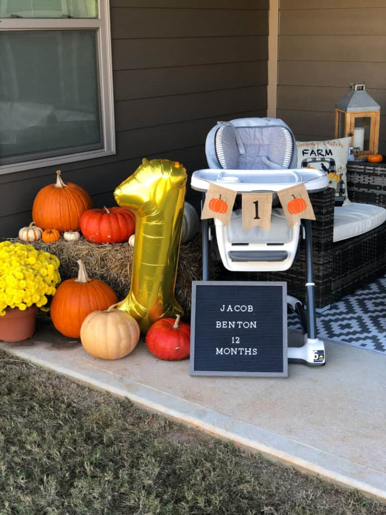 Outdoor party decorations... pumpkins on a hay stack, a birthday board, and the high chair with a pumpkin banner