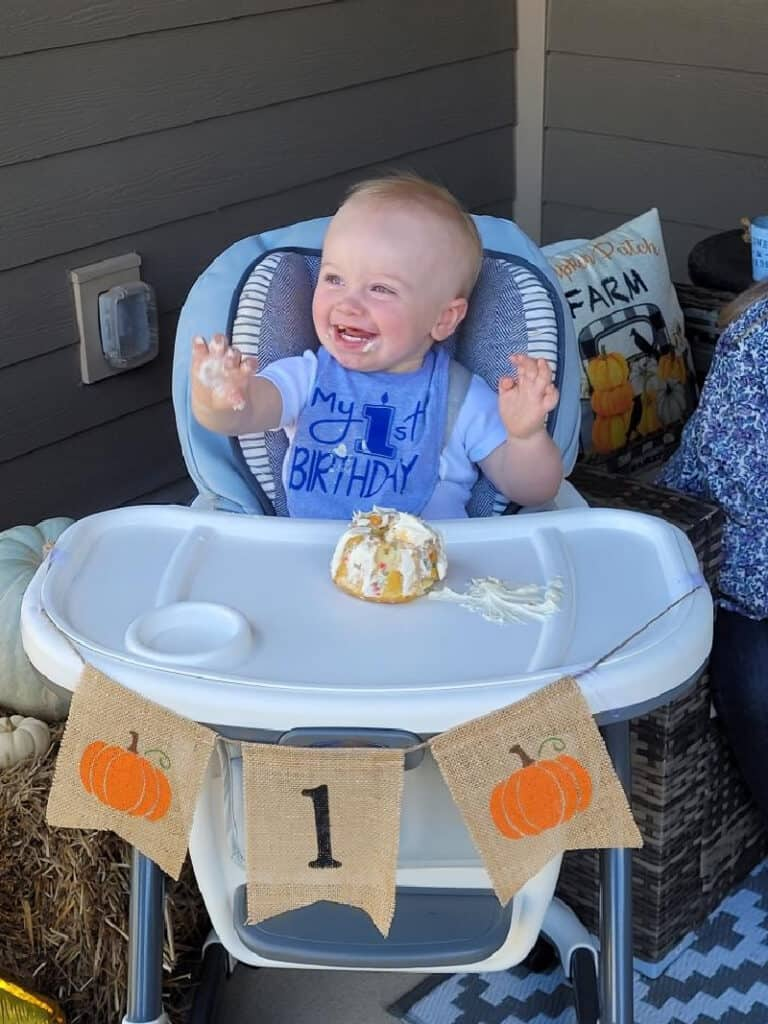 Jacob with a big smile and his hands in the air as he eats his cake.