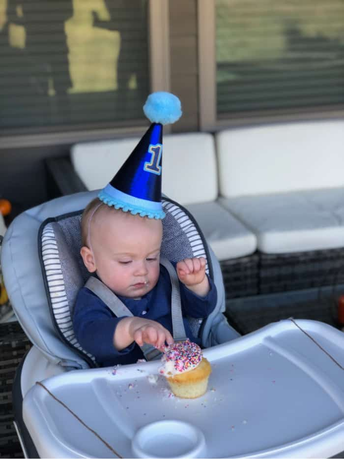 Jacob in his high chair about to eat a sprinkle cupcake