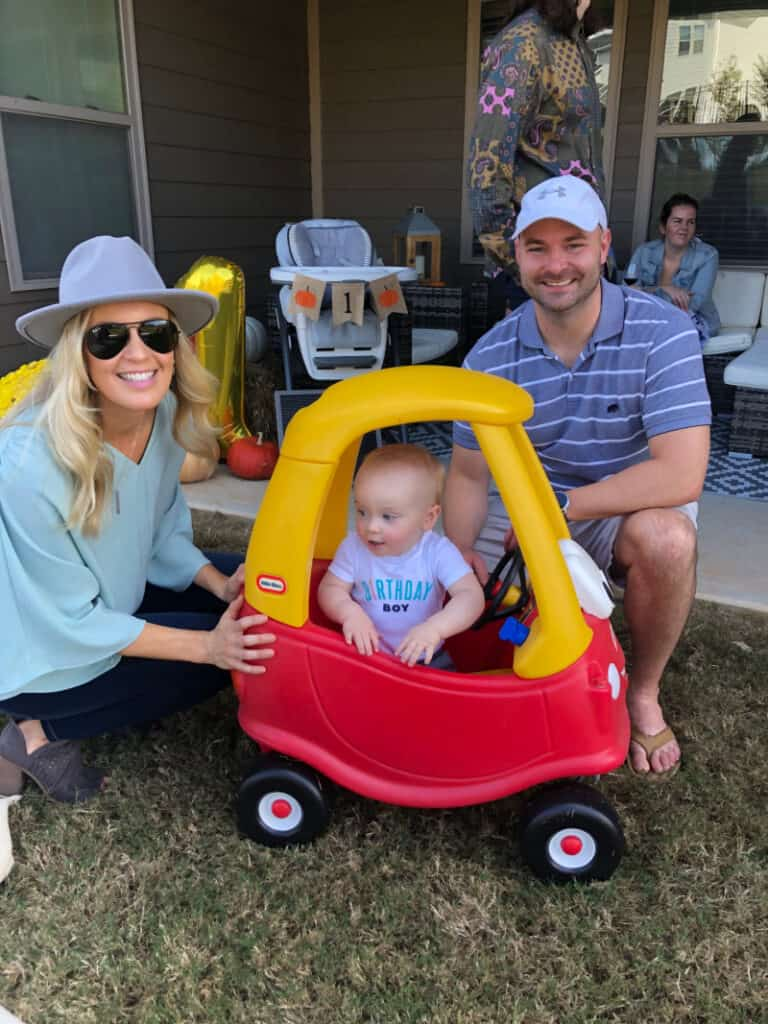 Lindsey and Joey next to Jacob as he rides in his car in the backyard.