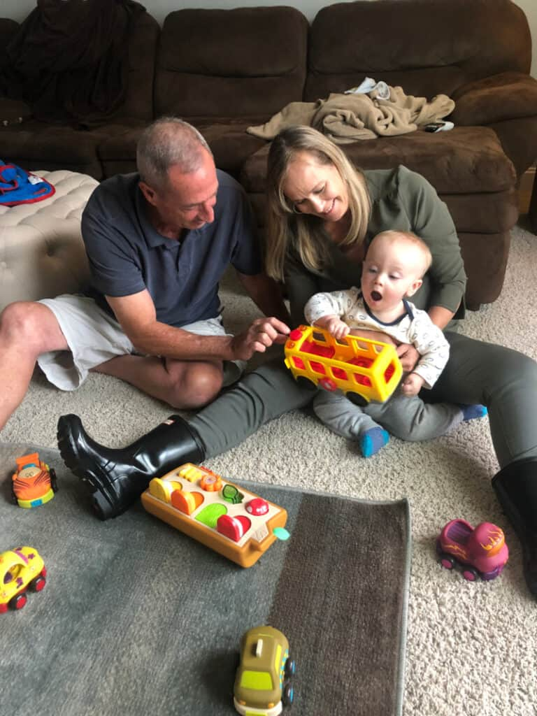 A very happy Jacob playing with his gifts on the floor with Grammy & Grampy.