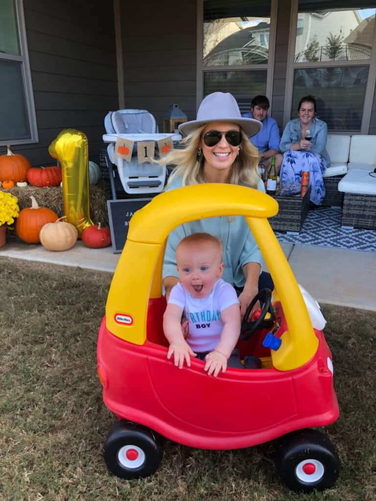 Lindsey with Jacob as he smiles big in his car.