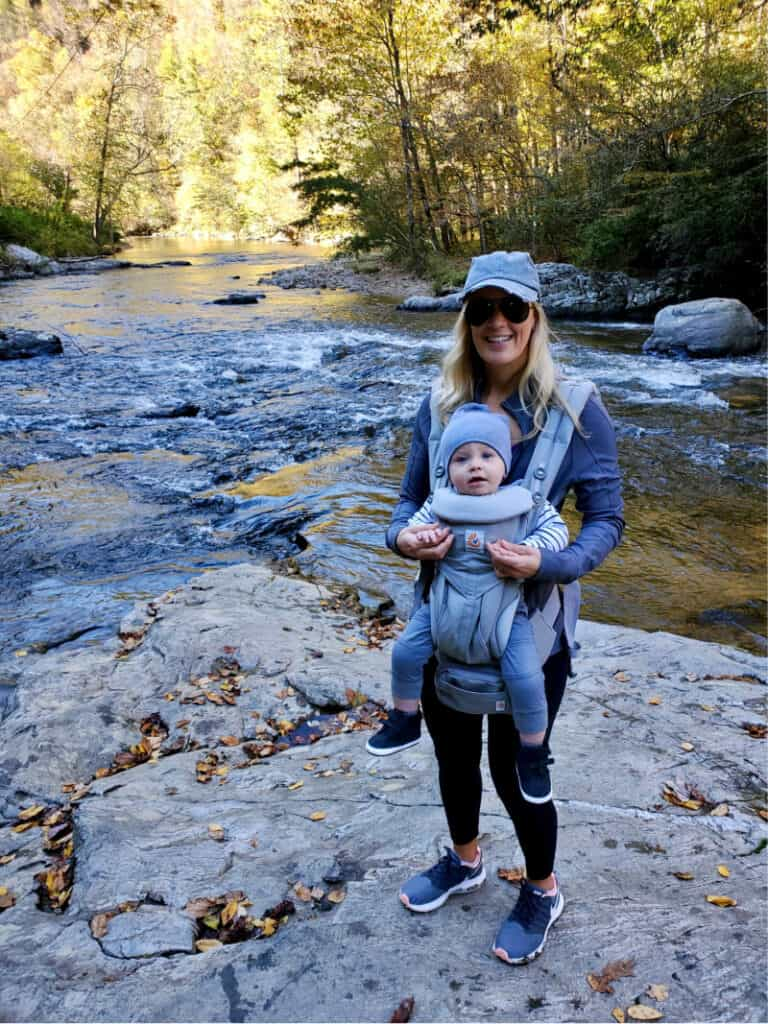 Lindsey with Jacob in the ergo carrier on the rocks on the river