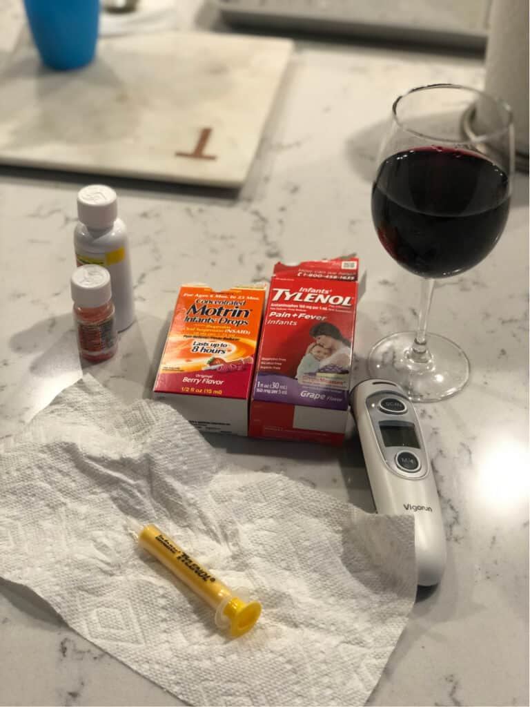 Infant tylenol, infant motrin, thermometer and a glass of wine on the counter