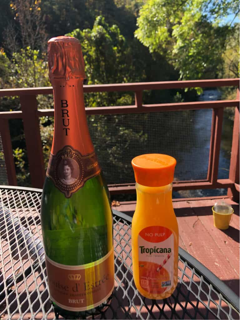 A bottle of champagne and orange juice on the balcony