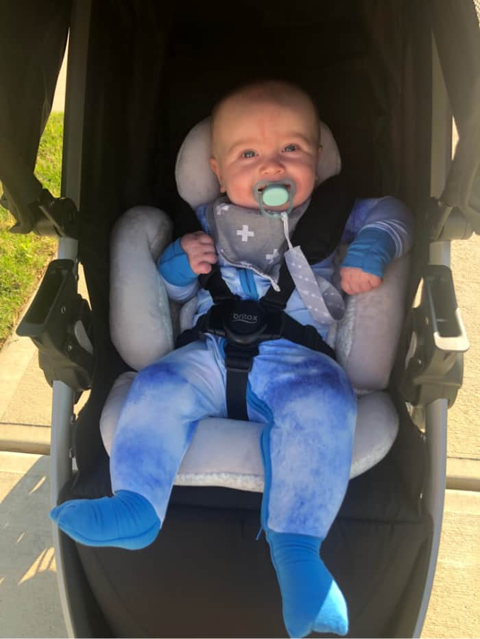 Jacob in his blue zip pajamas in the stroller.