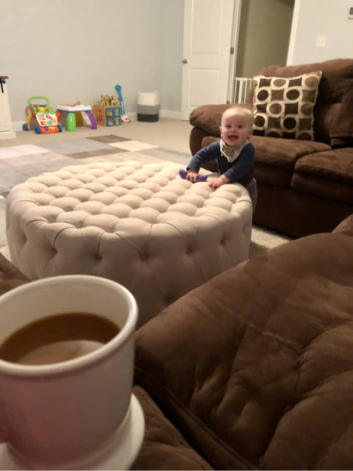 Jacob standing next to the ottoman smiling in the playroom as Lindsey holds her cup of coffee