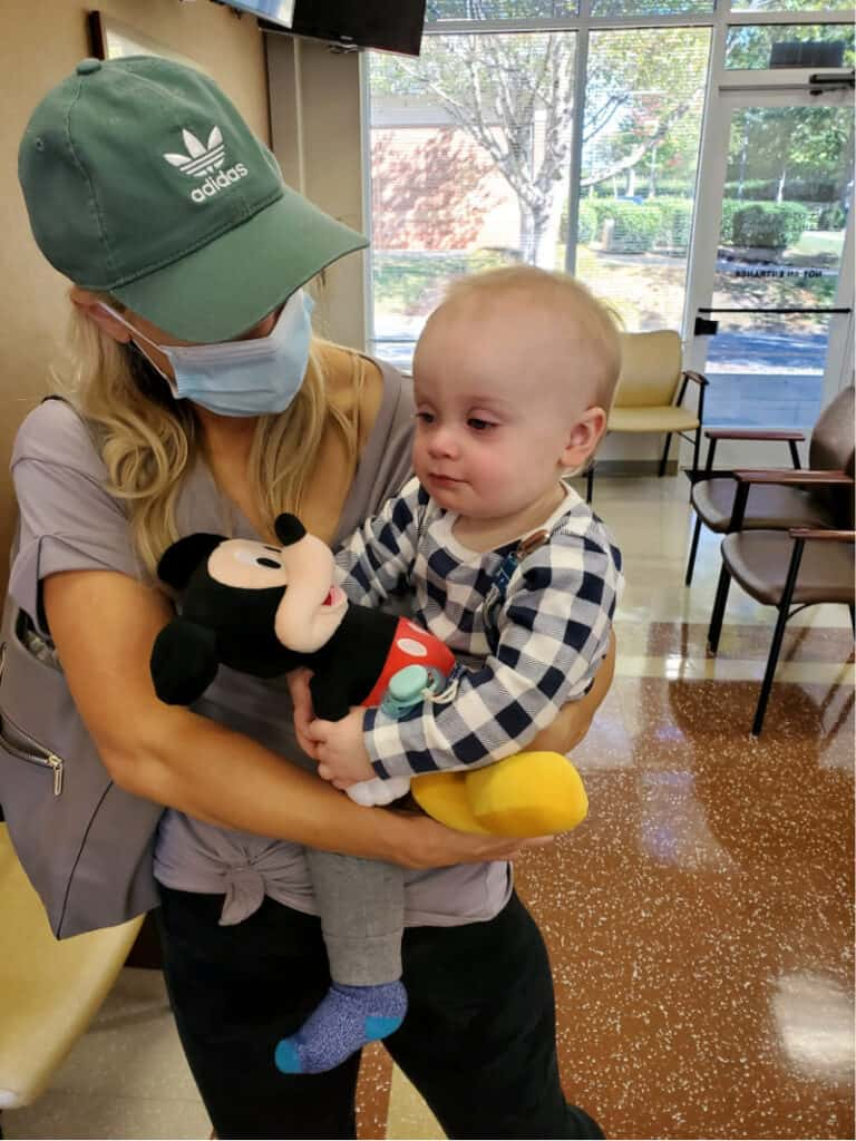 Lindsey holding Jacob at Urgent Care as he snuggles Mickey Mouse.