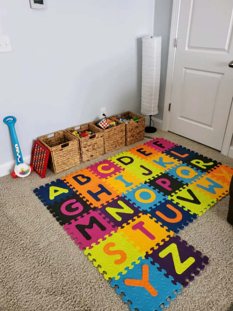 Alphabet mat and cubes lined up against the wall full of toys.