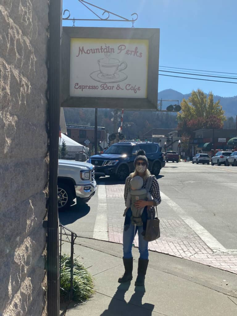 Lindsey wearing a mask and holding Jacob in then baby carrier in front of Mountain Perks coffee shop.