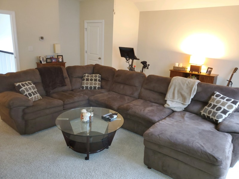 The large, brown couch and glass coffee table in the mancave.