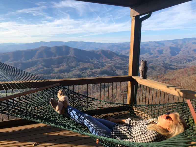 Lindsey laying in the porch hammock with an incredible mountain view.