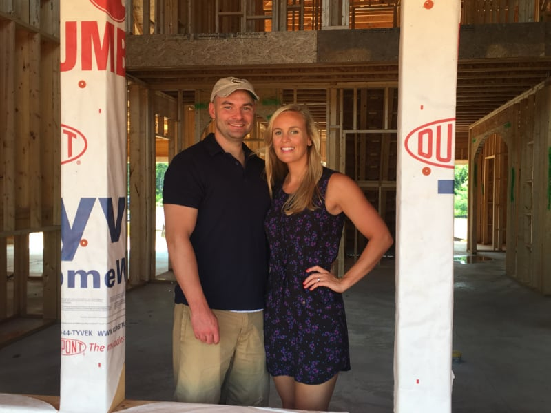 Joey and Lindsey standing in a window of their house in the building stages