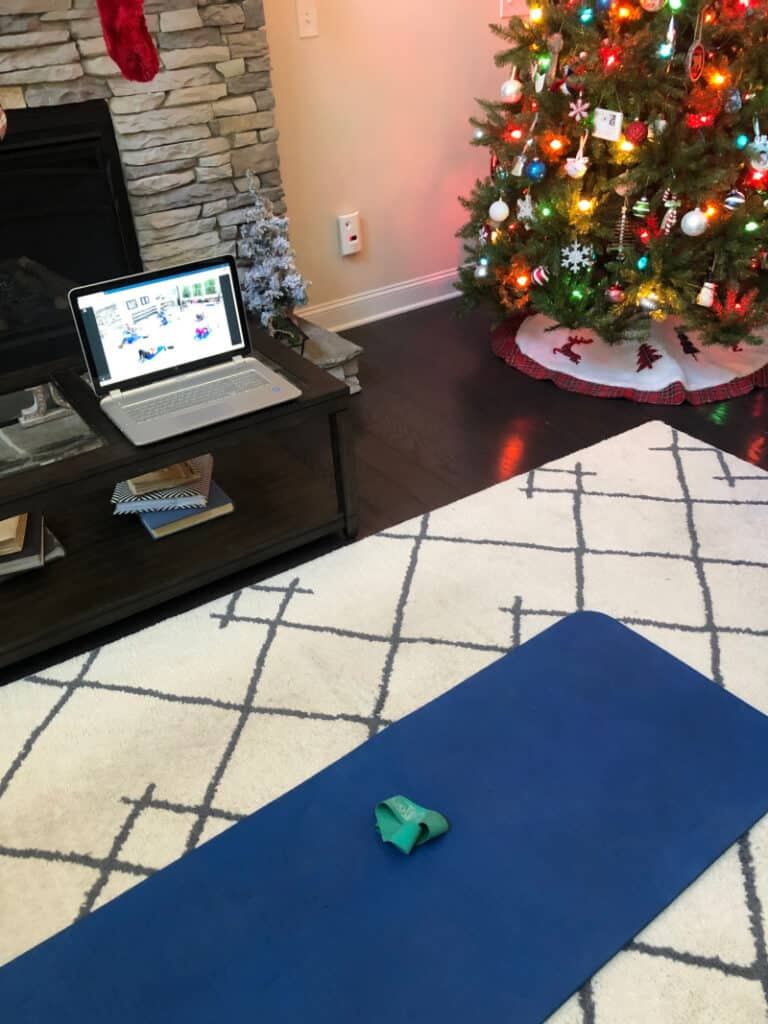 The laptop set up on the coffee table by the Christmas tree and a yoga mat on the floor.