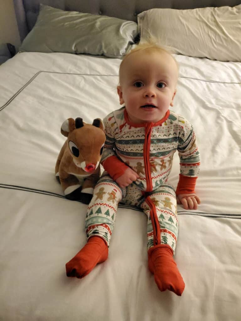 Jacob sitting on the bed in his Christmas pjs with Rudolph