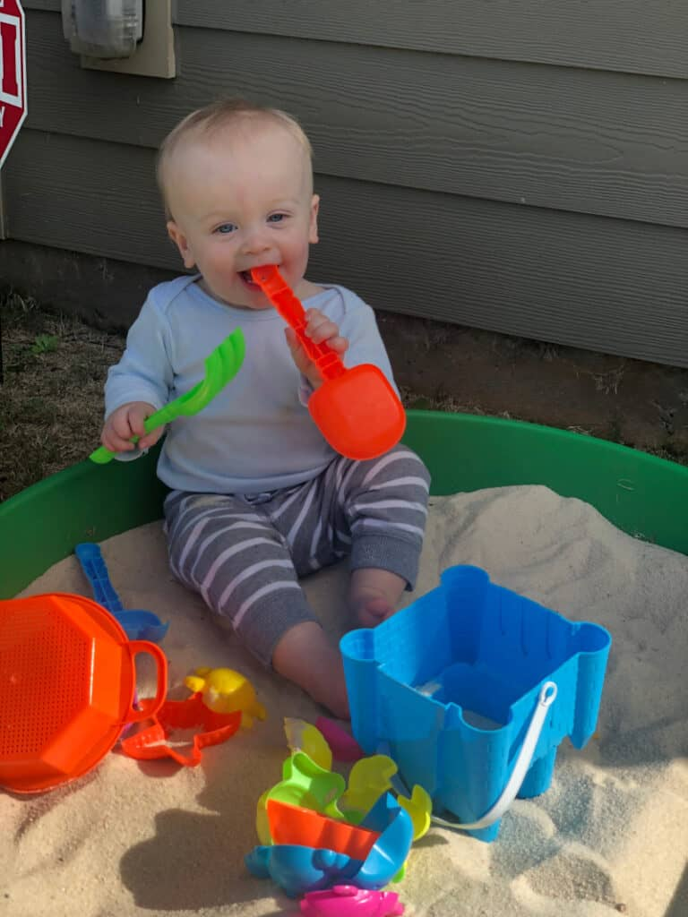Jacob in the sandbox with a shovel in his mouth.