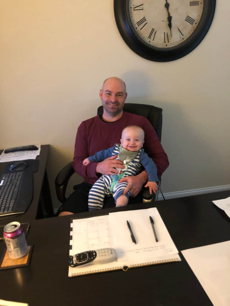 Jacob with a big grin in Joey's lap in the home office