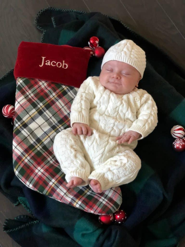 Newborn Jacob laying next to his stocking.