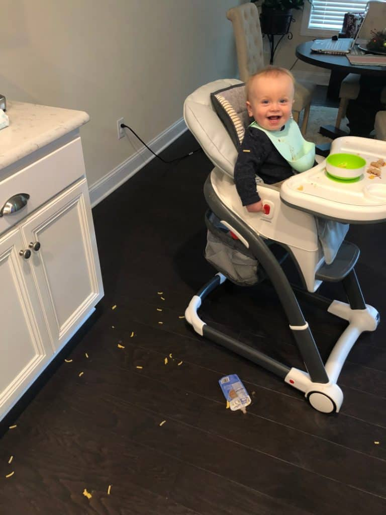 Jacob smiling in his highchair about all the food he threw on the floor