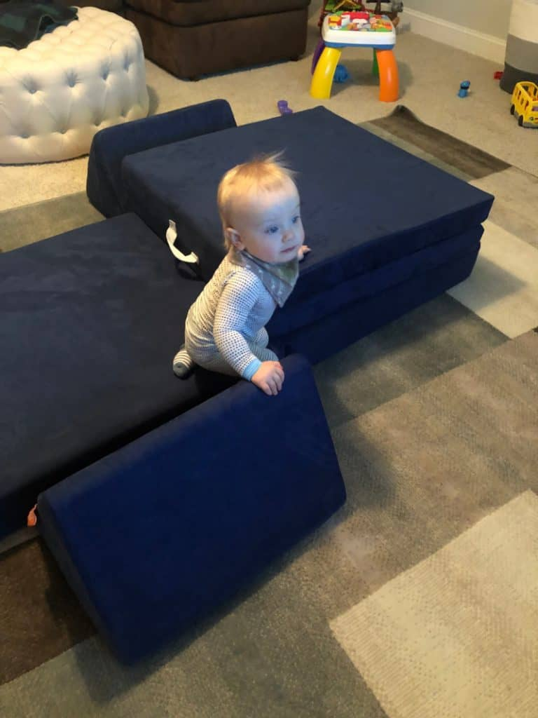 Jacob climbing on the blue nugget couch in the playroom.