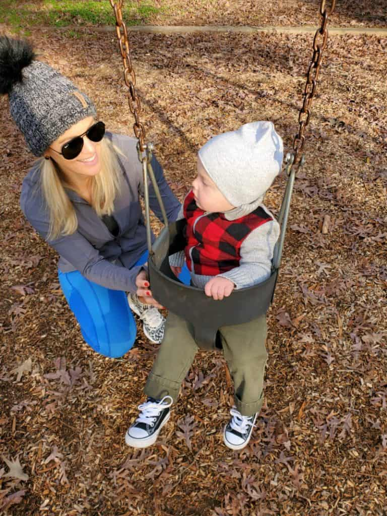 Jacob swinging at the park and Lindsey smiling next to him