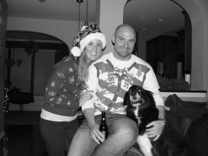 Joey and Lindsey in ugly Christmas sweaters and Bentley smiling with them