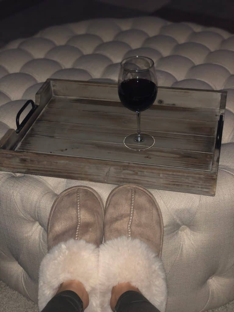 Lindsey's slippers on the ottoman and a glass of red wine